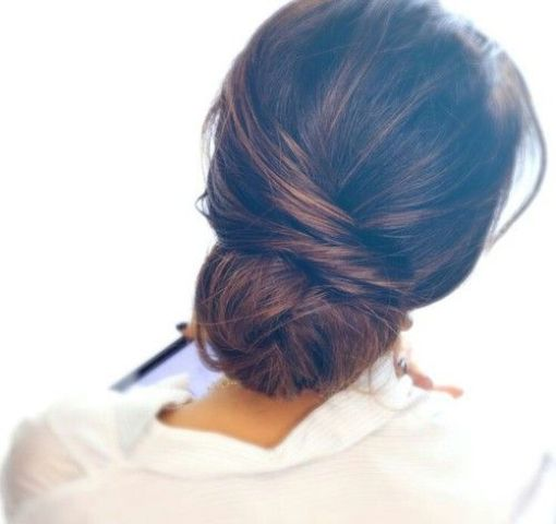 a messy twisted low bun with a bump and some locks for a gorgeous modern or boho bridal look