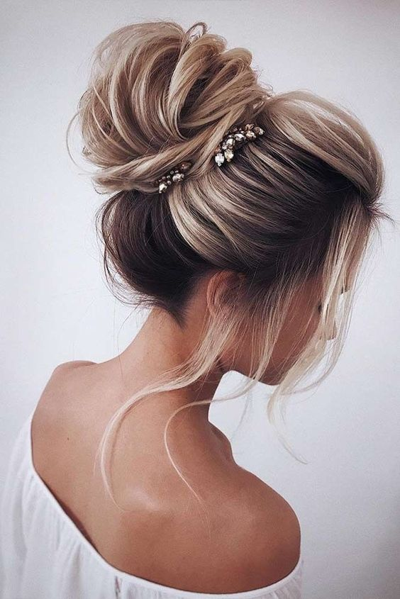 a voluminous and textural top knot with a bump, some locks down and a couple of thinestone hairpieces