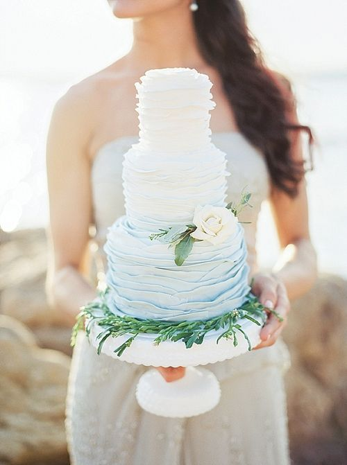 an ombre blue ruffle wedding cake decorated with greenery and a white bloom for an oceanside wedding