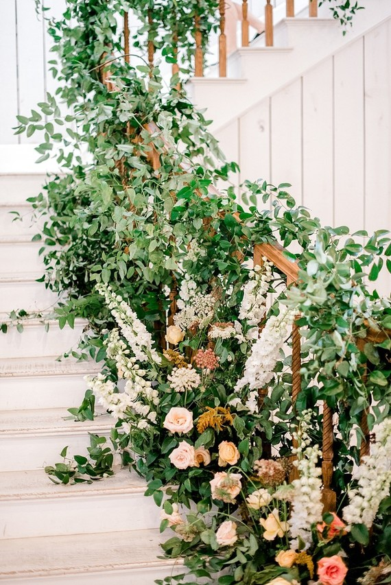 The barn was decorated with lush greenery and neutral blooms inside