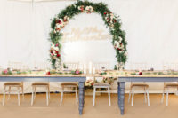 08 The reception space was done with rustic touches, bold blooms, greenery and many candles