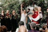 08 The wedding arch was made of greenery and burgundy blooms and cascading pale plants were hanging from above
