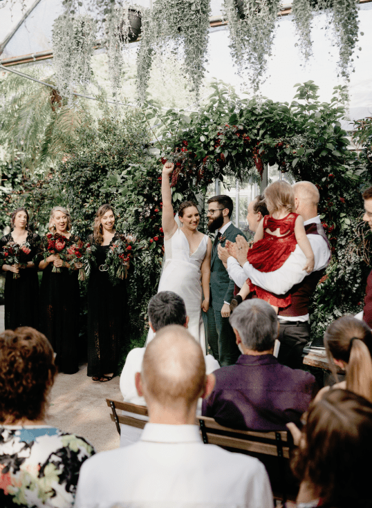 The wedding arch was made of greenery and burgundy blooms and cascading pale plants were hanging from above