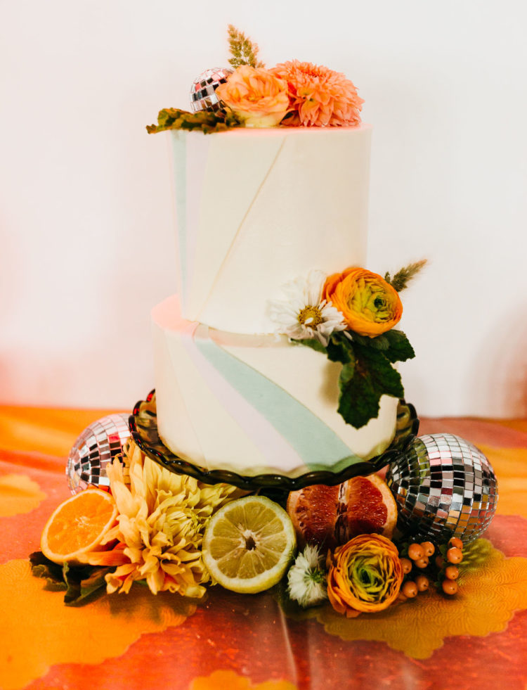 The wedding cake was a geometric one, with colorful blooms and citrus at the base