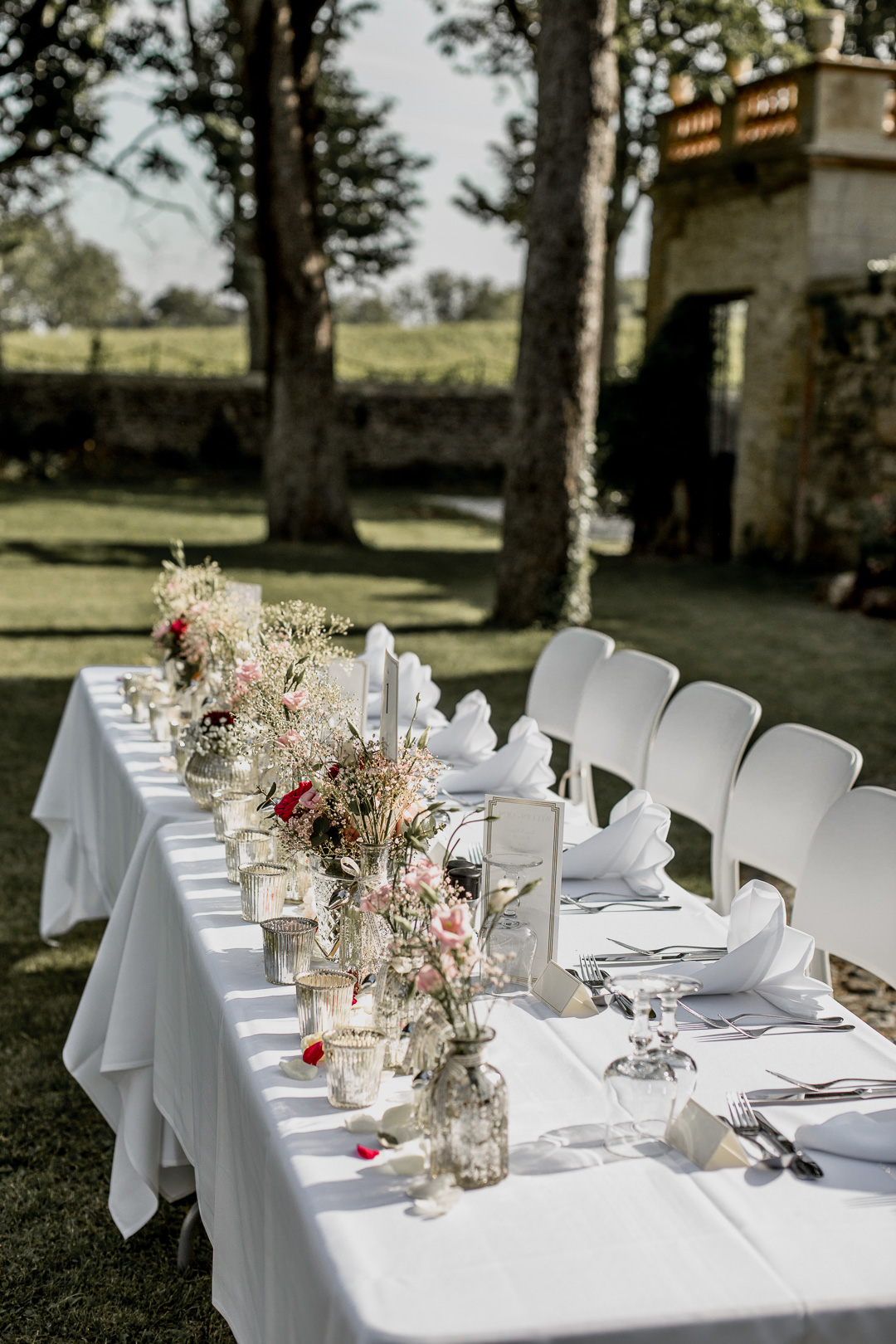 The wedding reception tables were done with delicate florals, white textiles and mercury glass vases and candle holders