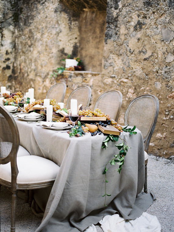 The wedding table was styled with a grey tablecloth and done with a runner with books, grapes, berries, candles and pears