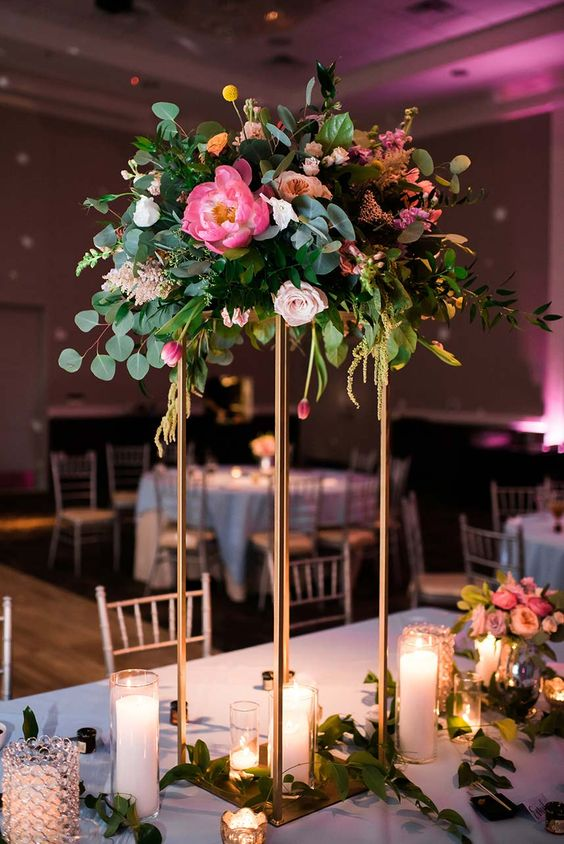 a gorgeous tall centerpiece with pink and blush blooms, craspeadia, greenery on a brass stand with candles around