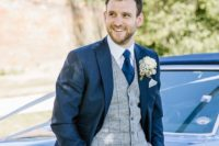 08 a navy suit with a grey checked waistcoat and a navy tie plus a lush white floral boutonniere