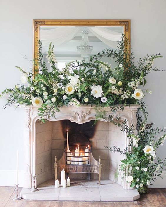 an exquisite fireplace with candles inside it, a vintage framed mirror and lush greenery and white blooms