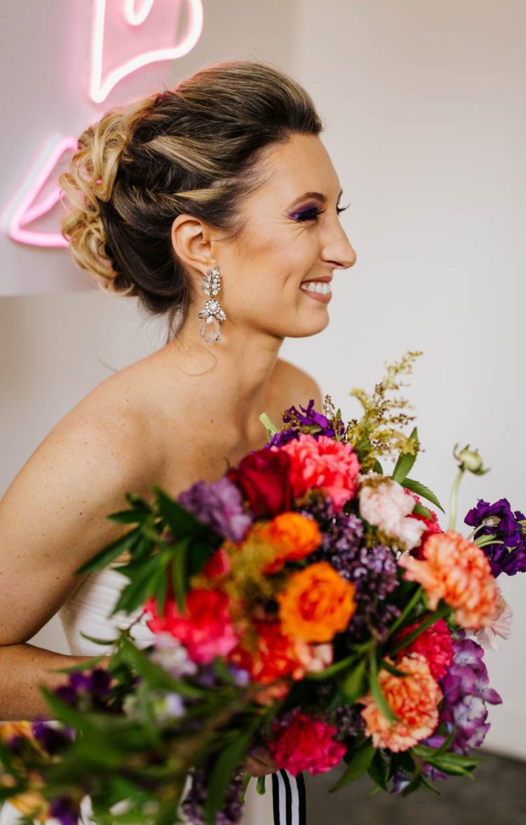 The wedding bouquet was done with pink, orange, purple and greenery plus striped ribbons