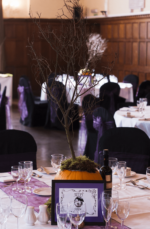 The wedding decor was done with purple, orange and dried branches and moss