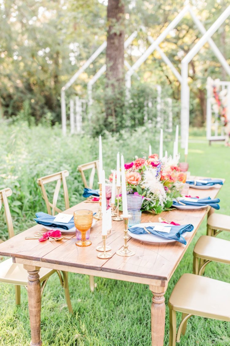 The wedding tablescape was done with blue napkins, pink bows, gilded touches and colored glasses plus lush florals