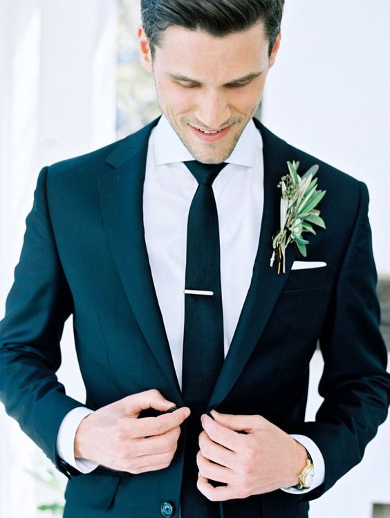 a modern black suit, a white shirt and a black tie is classics that will fit many wedding styles