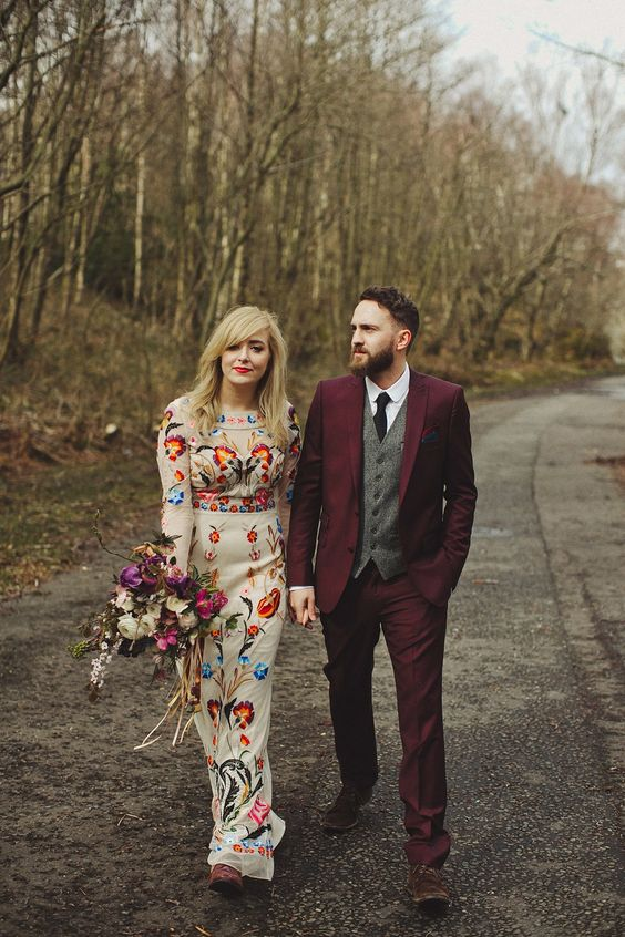 a sheath wedding dress with colorful floral embroidery, burgundy suede boots and a red lip