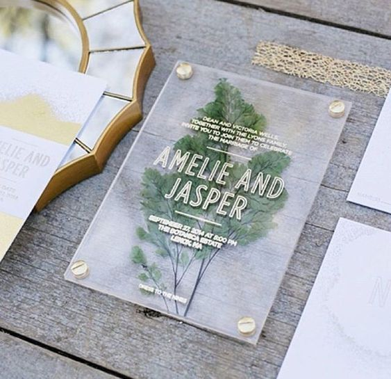 an acrylic wedding invitation with a pressed lead and gold letters looks very modern
