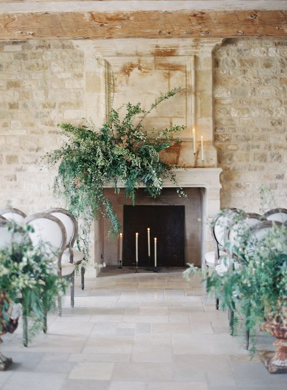 an elegant fireplace with candles inside and on the mantel and a lush greenery decoration