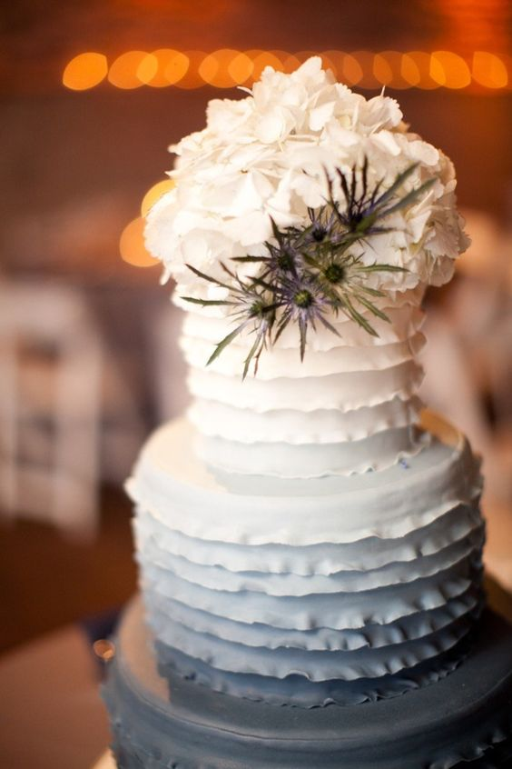 an ombre white to grey ruffle wedding cake topped with white hydrangeas and blue thistles