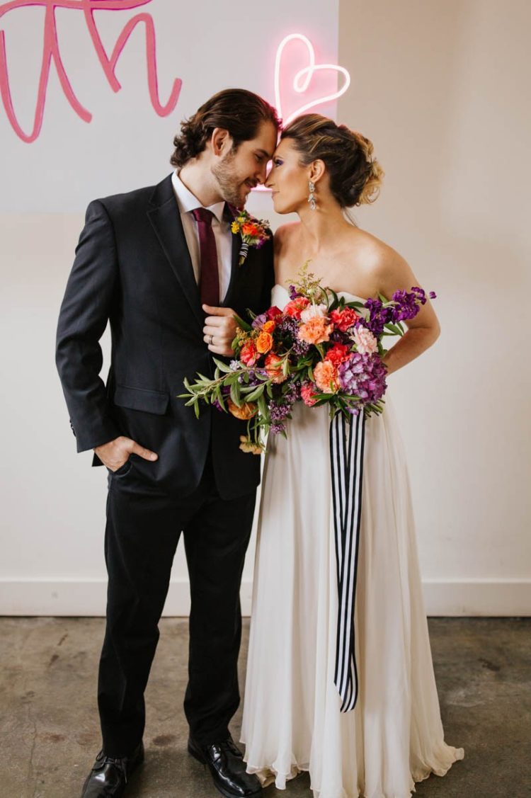The groom was wearing a black suit, a burgundy tie and a colorful floral boutonniere