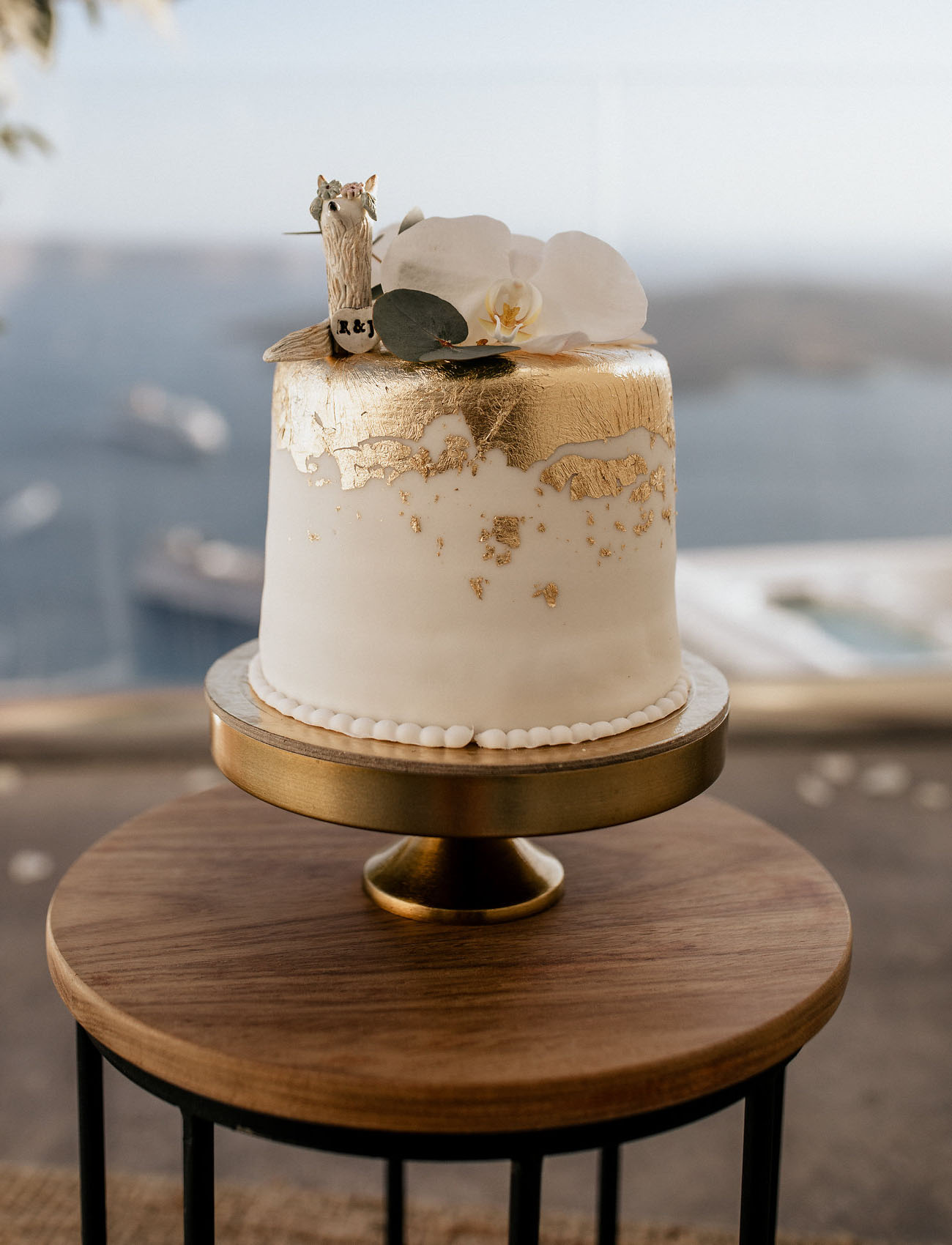 The wedding cake is a white one with gold leaf, topped with a white orchid