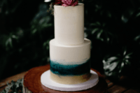 10 The wedding cake was a white one with ombre teal and gold plus some bright blooms on top