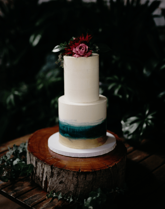The wedding cake was a white one with ombre teal and gold plus some bright blooms on top