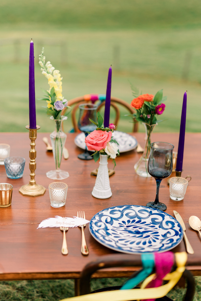 The wedding tablescape was done with many candles, bright blooms and printed plates