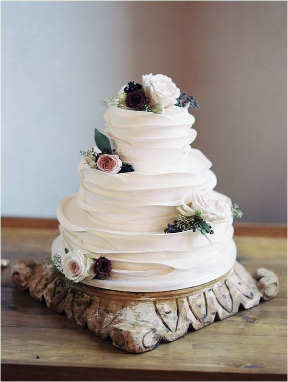 a beautiful white ruffle wedding cake with blooms and leaves for a modern rustic wedding