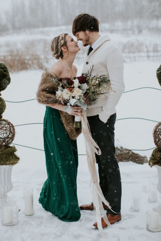 a chic coordinating look with a green wedding gown and a fur stole and a relaxed groom's look with a creamy cardigan