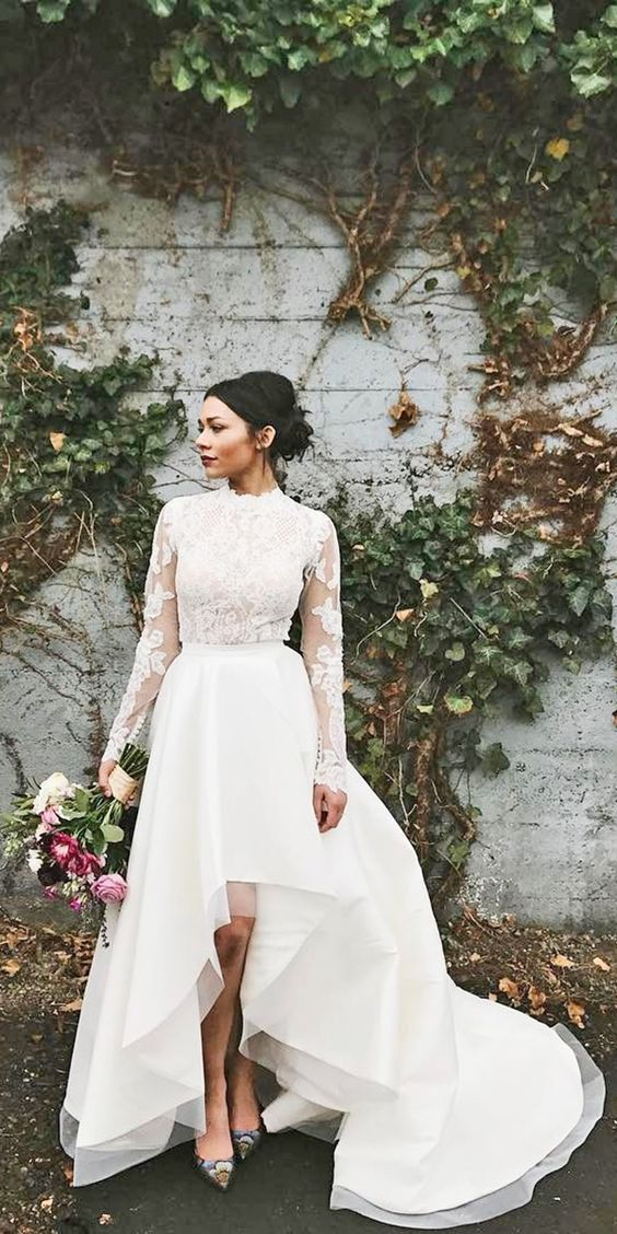 a glam bridal look with a lace applique wedding top with long sleeves and a high low layered skirt with a train plus printed shoes