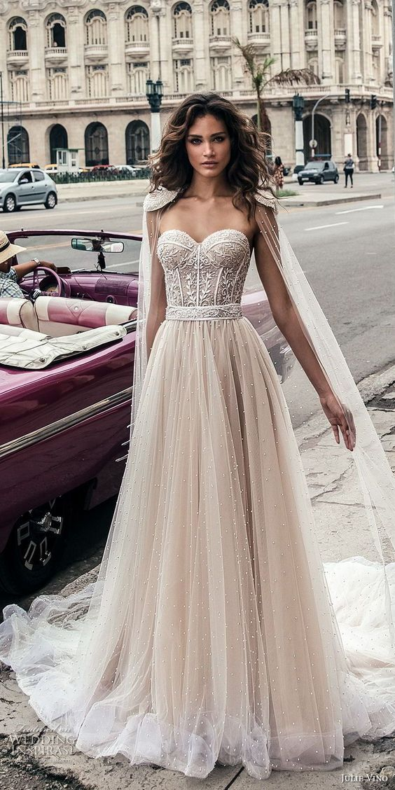 a beautiful nude wedding dress with a lace sweetheart neckline bodice and a pearled skirt plus a matching cape