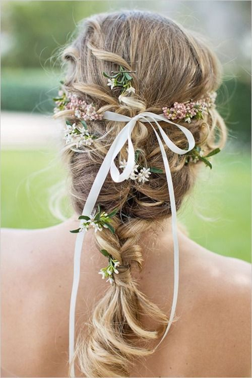 a braid with some curls and some blooms and greenery plus a thin ribbon