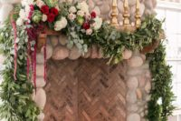 11 a fireplace clad with tiles and stone, with candles inside and a lush greenery and bloom garland on top