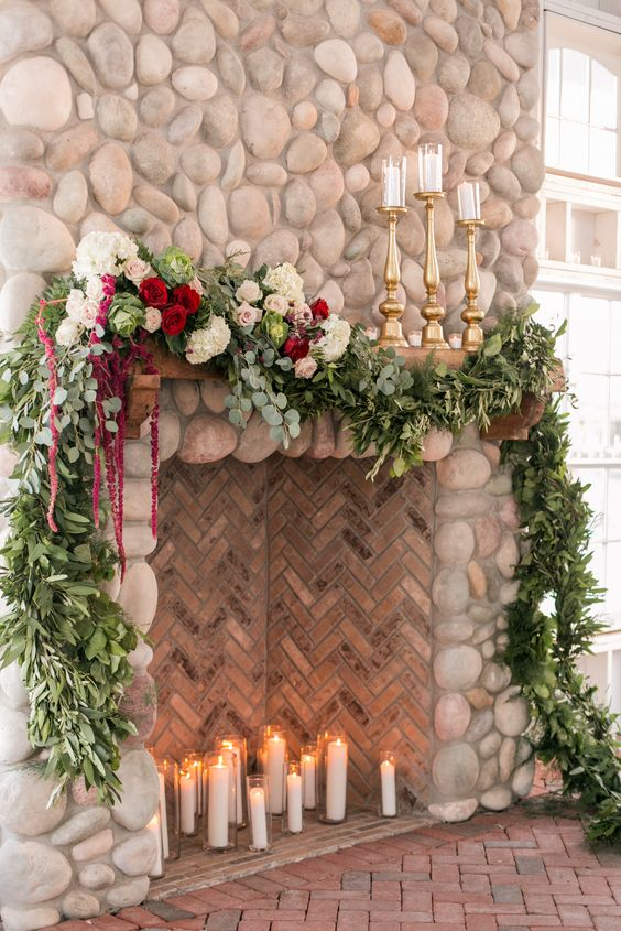 a fireplace clad with tiles and stone, with candles inside and a lush greenery and bloom garland on top