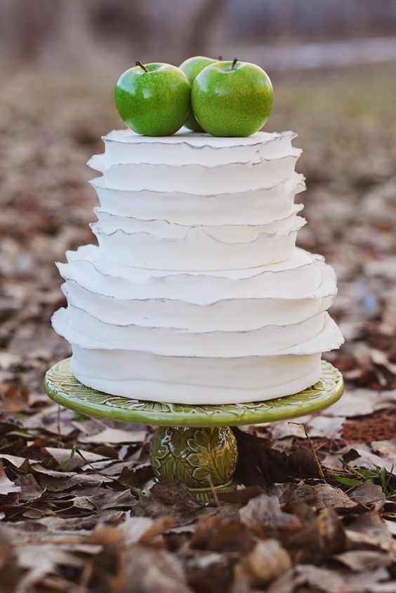 a cool white ruffle wedding cake with silver edges and green apples on top for a fall wedding