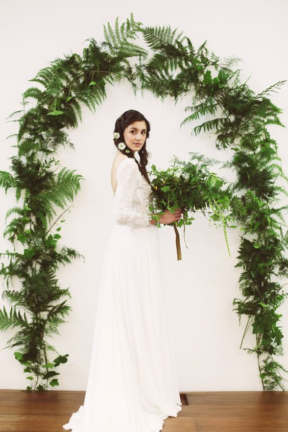 a fern and foliage wedding arch and a matching bouquet will make an indoor space feel like outdoors