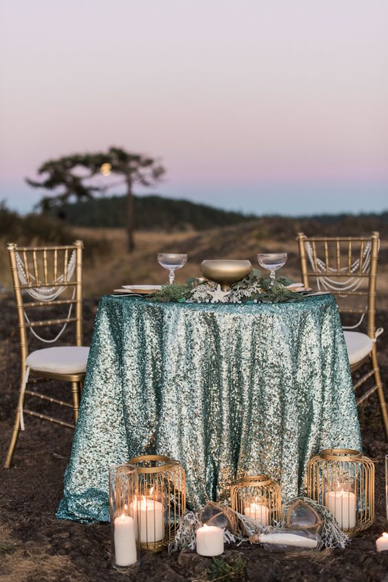 a mermaid table setting with an aqua sequin tablecloth and touches of brass for a chic look