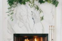 12 a modern working marble clad fireplace with greenery, white blooms and thin and tall candles