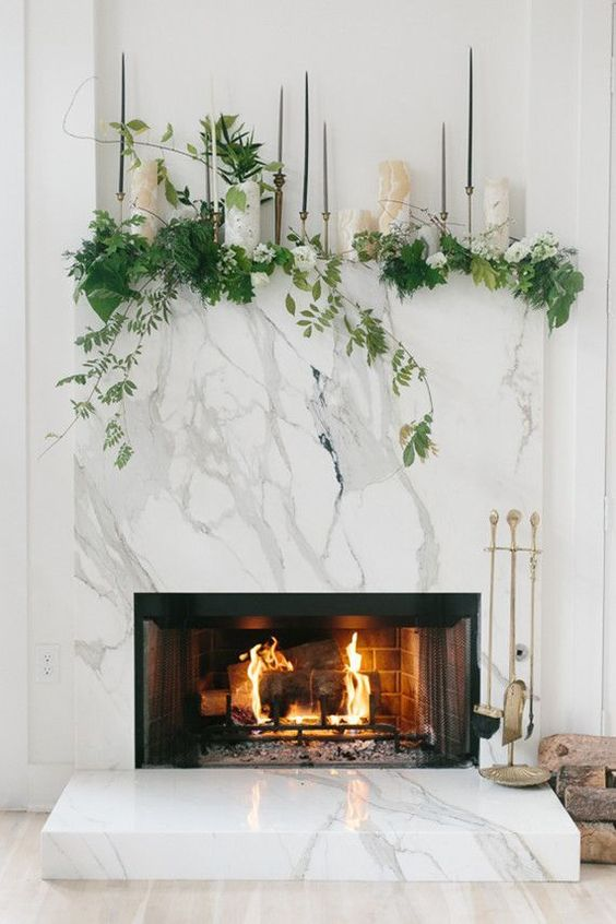 a modern working marble clad fireplace with greenery, white blooms and thin and tall candles