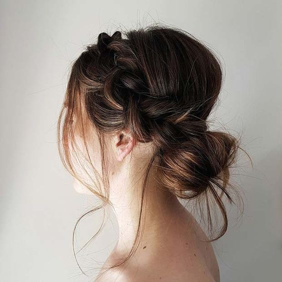 an elegant yet messy low bun with a side braid and some locks down for a cool look