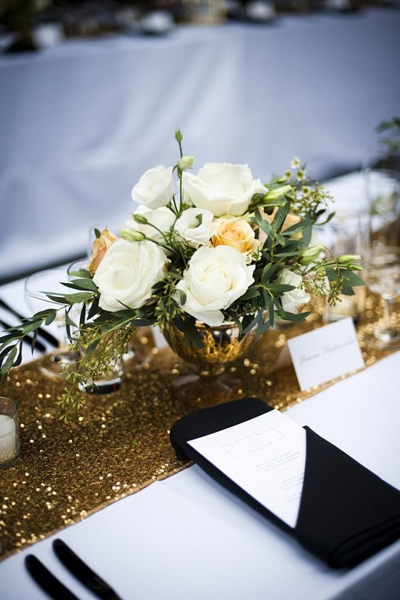 a black and white tablescape is spruced up with a gold sequin table runner for a bold touch