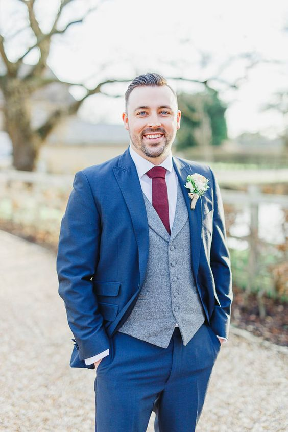 a bold blue suit, a grey waistcoat and a burgundy wide tie for a bright outfit