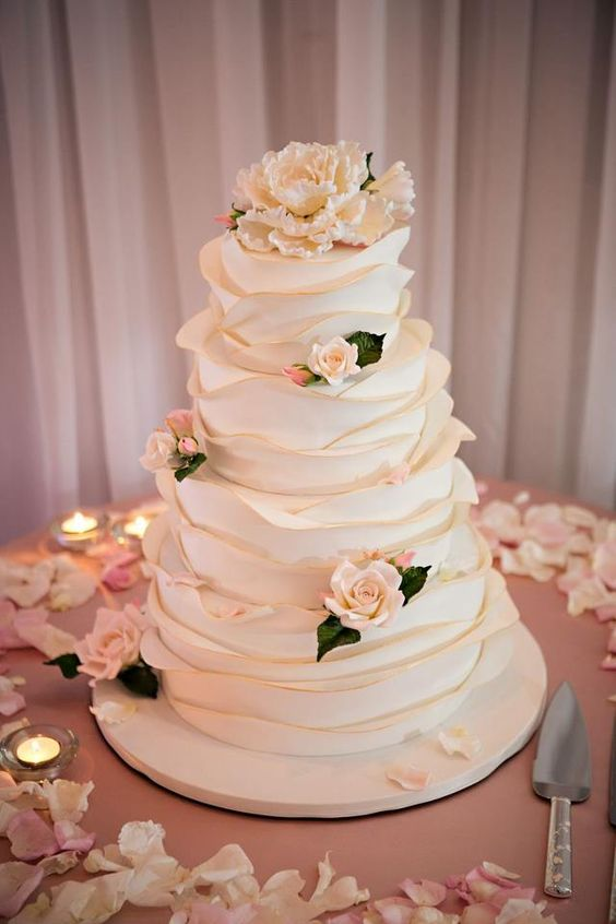 a cute neutral wedding cake with textural large ruffles and sugar blooms all over