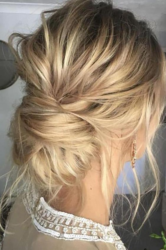 a messy low chignon hairstyle with lots of hair down for ane ffortlessly chic look