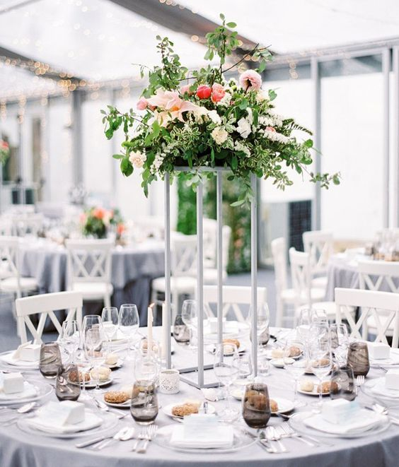a modern tall centerpiece with textural greenery, pink and white flowers on a white stand