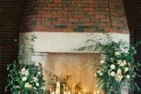 13 a refined fireplace with candles all around and lush greenery and white blooms incorporated