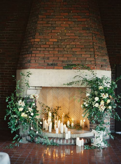 a refined fireplace with candles all around and lush greenery and white blooms incorporated