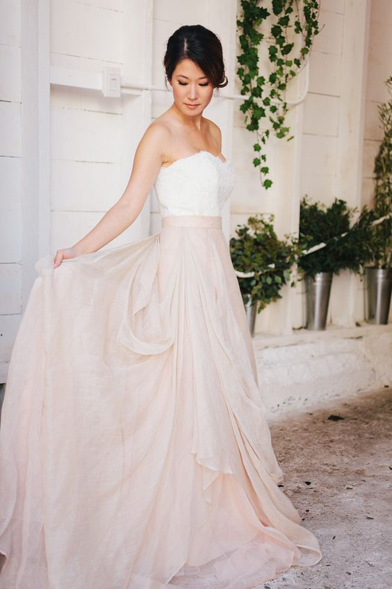 a romantic bridal look with a lace strapless top and a blush draped maxi skirt
