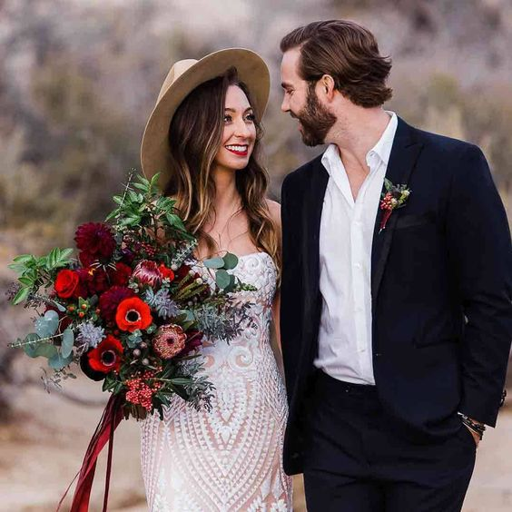 a strapless boho wedding dress plus a hat and a black suit with no tie to match