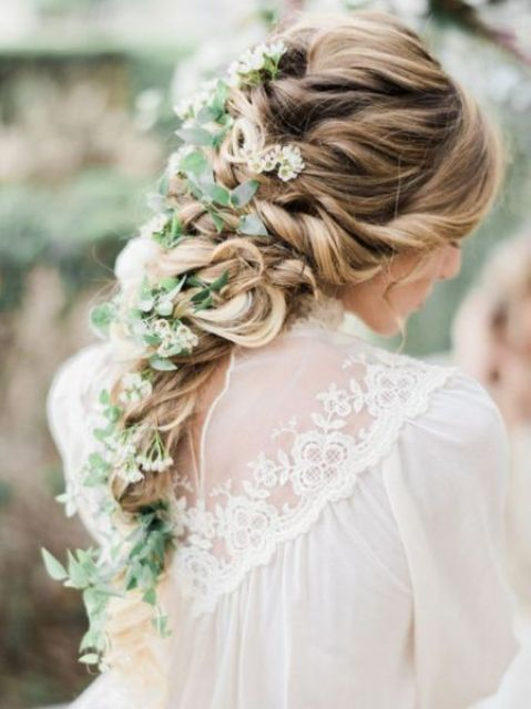 a twisted and curled braid with a texture on top and greenery and whiet blooms in the braid