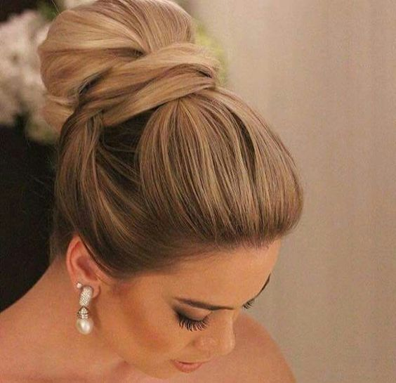 an elegant and sleek top knot with twisted elements and a bump on top for a formal wedding